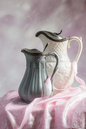Two antique Victorian jugs on a table with pink ribbon and cloth Stock Photo