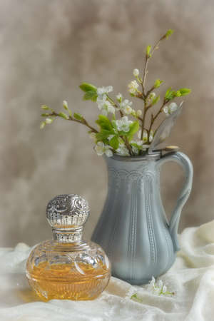 Antique perfume bottle with antique jug filled with spring blossom Stock Photo