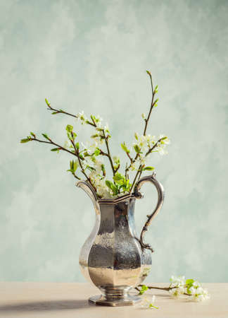 edwardian: Antique silver jug filled with spring blossom