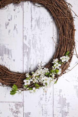 green door: Apple blossom garland on white wooden door Stock Photo