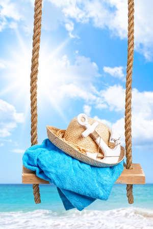 sun beach: Summer swing with beach towel and anchor against an ocean blur background Stock Photo