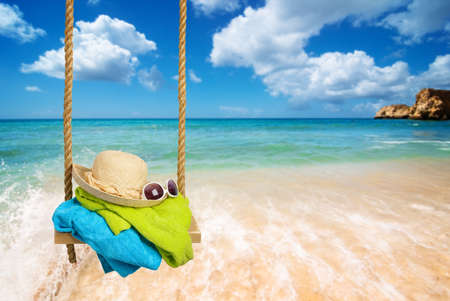 sun beach: Summer rope swing with beach towels, sunhat and shades with beach blur background