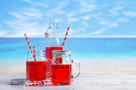 cordial: Summer fruit drinks with beach blur background