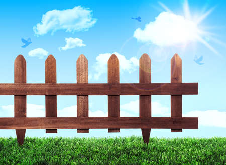 home and garden: Garden fence with grass and summer sky Stock Photo