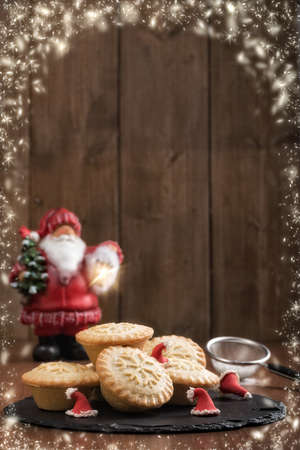 fayre: Mince pies on slate tray decorated with santa hats Stock Photo