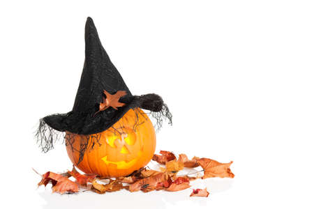 Jack O Lantern sitting on autumn leaves wearing a witches hat