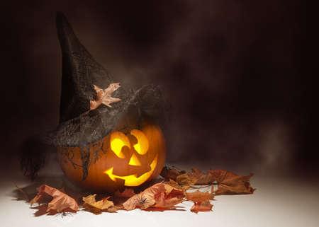 jack o  lantern: Glowing Jack O Lantern amongst autumn leaves Stock Photo