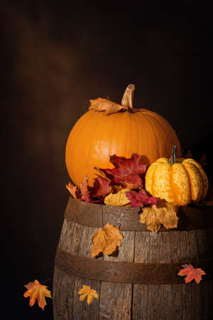 russet: Pumpkins sitting on rustic wooden barrel with fall leaves Stock Photo