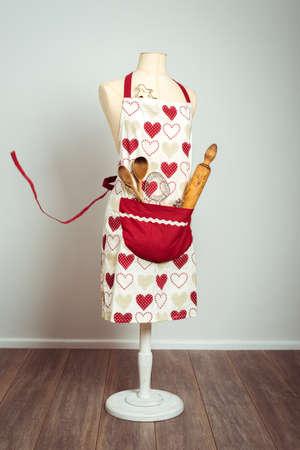mandil: delantal rojo con el bolsillo lleno de utensilios