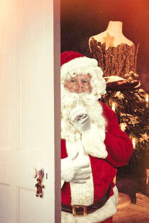 shush: Santa Claus saying shush at open door leading to festive Christmas setting