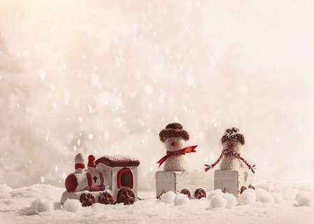 pull toy: Muñecos de nieve sentado en tren de juguete en Navidad en la nieve Foto de archivo