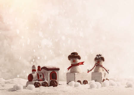 old fashioned: Snowmen sitting in toy train set at Christmas in the snow Stock Photo