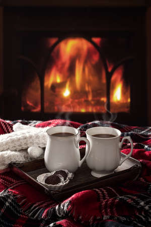 log cabin: Hot chocolate drinks by the fireside Stock Photo