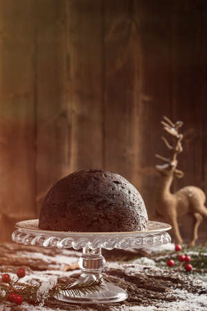Christmas pudding in snowy setting with creative lighting