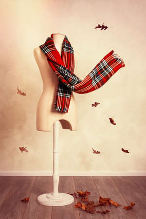 checkered scarf: Winter wool tartan scarf with falling leaves Stock Photo