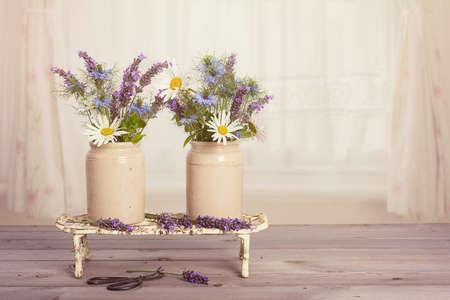 wild mint: Flower arrangement in vintage pots in window Stock Photo