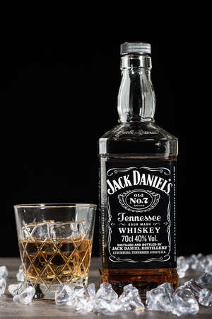 daniels: TELFORD, UK - JANUARY 22, 2016: A bottle of Jack Daniels Tennessee Whiskey on a black background. The Jack Daniels brand of owned by the Brown-Forman Corporation and operates from Moore County, Tennessee, USA