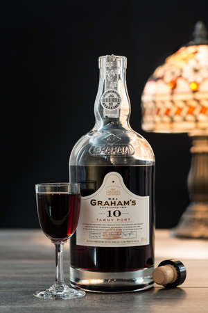 tipple: TELFORD, UK - JANUARY 22, 2016: A bottle of Grahams 10 Year Vintage Tawny Port on a black background. The Grahams brand is owned by Symington Family Estates based in Portugal Editorial