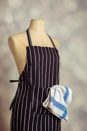 mandil: delantal de cocina en maniquí de la vendimia con teatowel en el bolsillo