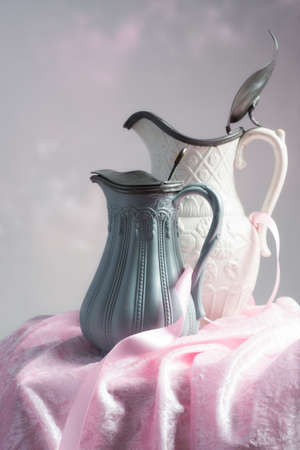 pewter: Antique Edwardian pottery jugs still life with pink ribbon