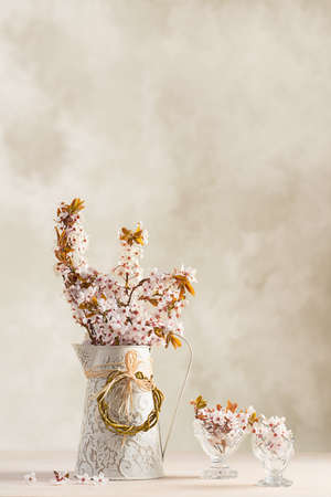 flower of life: Spring blossom in jug with filled antique glasses on wooden table