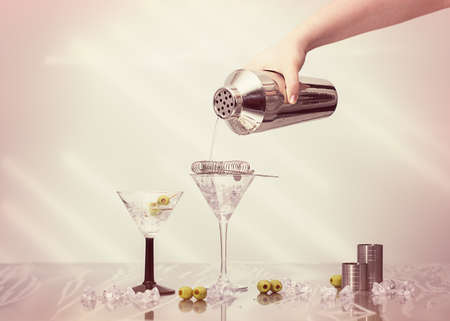cocktail strainer: Pouring cocktail drink from a shaker into Art Deco cocktail glasses