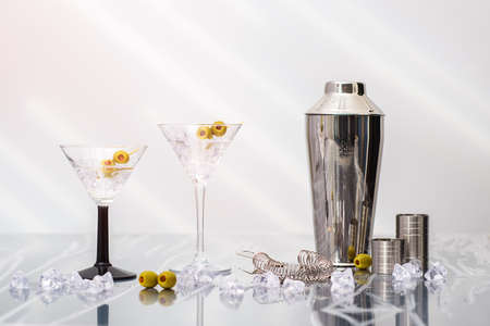 martini shaker: Two Martini cocktails poured over crushed ice in Art Deco glasses with shaker in the background