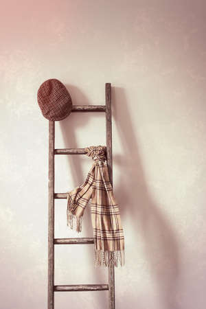 flat cap: Flat cap and scarf on rustic wooden ladder