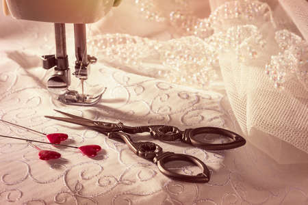 maquinas de coser: tijeras de costura con alfileres en forma de corazón en la tela de vestido de novia de encaje y - se centran en tijeras y alfileres