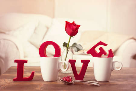 love letter: Red love letters in teacups with red rose in vase for Valentines Day - toned to give romantic vintage feel