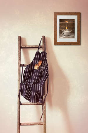 rungs: Kitchen apron hanging on the rung of a rustic wooden ladder with spoons and whisk