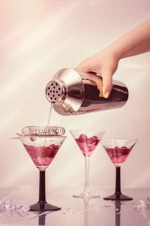cocktail strainer: Pouring cocktail drinks from a shaker into Art Deco cocktail glasses