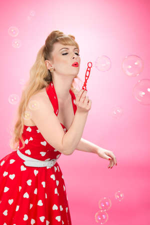 Pin up girl blowing bubbles on a pink background