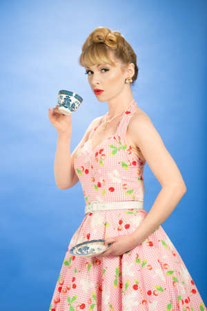halterneck: Pin up girl drinking from vintage teacup and saucer