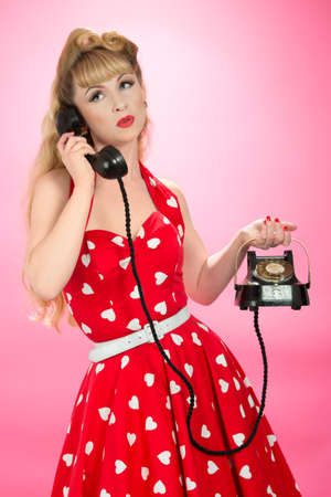 halterneck: Pin up girl with vintage telephone - close up on pink background