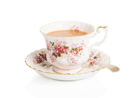 Taza de té del desayuno Inglés en taza de té de la vendimia y el plato con cuchara antiguo sobre un fondo blanco