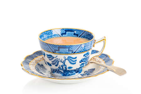 Cup of breakfast tea in antique teacup and saucer with spoon on a white background Stockfoto