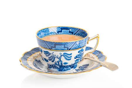 taza de té: Taza de té del desayuno en taza de té antiguos y plato con cuchara sobre un fondo blanco