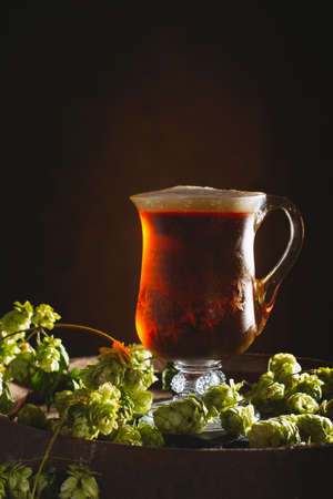 real ale: Antique glass tankard filled with ale on a rustic barrel with hops Stock Photo