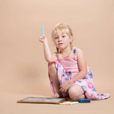 white chalks: Little girl playing with chalks on her chalk board