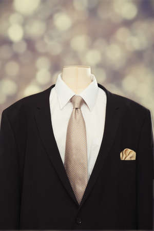 Close up of a mans suit and tie with white shirt and gold colored hankerchief