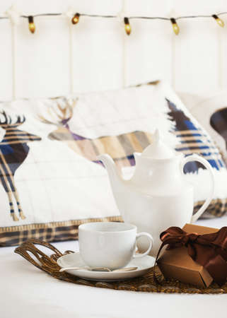 tied in: Breakfast tea in bed with Christmas gift tied with ribbon Stock Photo
