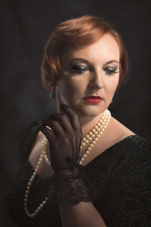 lace gloves: Young woman wearing black lace gloves and pearl necklace Stock Photo