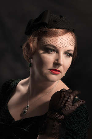 lace gloves: Twenties style portrait of glamorous woman wearing a pillar box hat and black lace gloves Stock Photo
