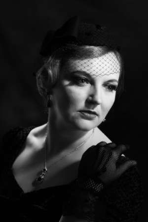 lace gloves: Twenties style black and white portrait of glamorous woman wearing a pillar box hat and black lace gloves