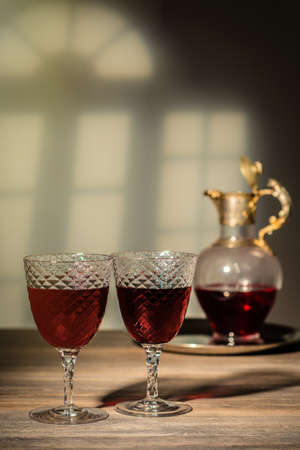 Two antique glasses filled with claret with decanter in the background