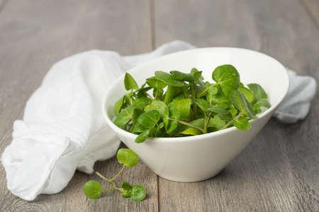 Fresh watercress in a bowl with white napkin Stock Photo