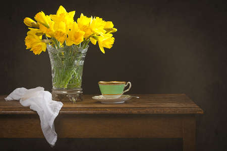 Still life with antique glass vase filled with spring daffodils on rustic table Stock Photo