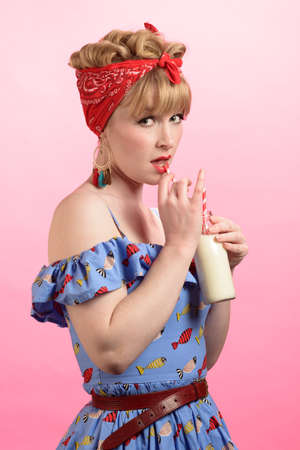 Cheeky pin up pose of woman wearing vintage style clothing with bottle of milk