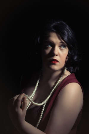 femme fatale: Portrait of young woman holding a pearl necklace